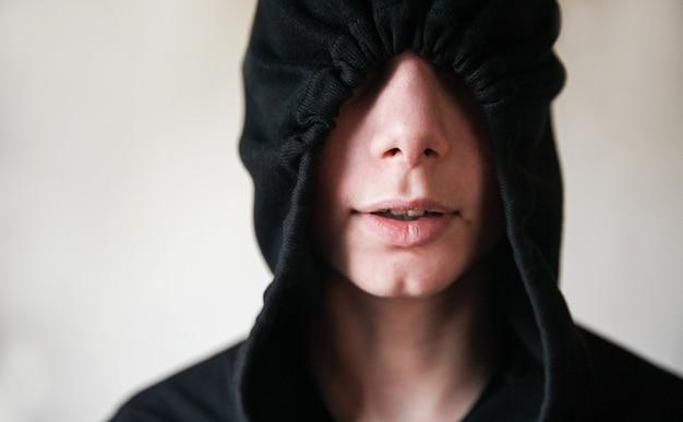 Een tienerjongen met een zwarte kap die het bovenste deel van zijn gezicht bedekt