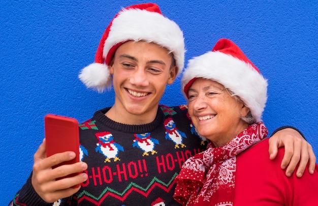 Een tienerkleinzoon knuffelt zijn grootmoeder en glimlacht terwijl hij naar zijn mobiele telefoon kijkt terwijl hij voor een blauwe muur staat, met een kersttrui en een kerstmuts op. concept van familie, vriendschap en plezier