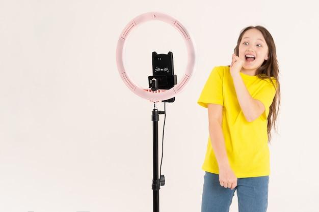Een tienermeisje danst en schiet een video op een witte achtergrond