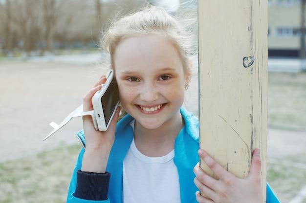 Een tienermeisje dat aan de telefoon praat en buitenshuis lacht