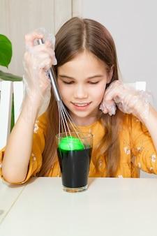 Een tienermeisje dat handschoenen draagt, verft eieren met behulp van een culinaire garde om geen handen vuil te maken.