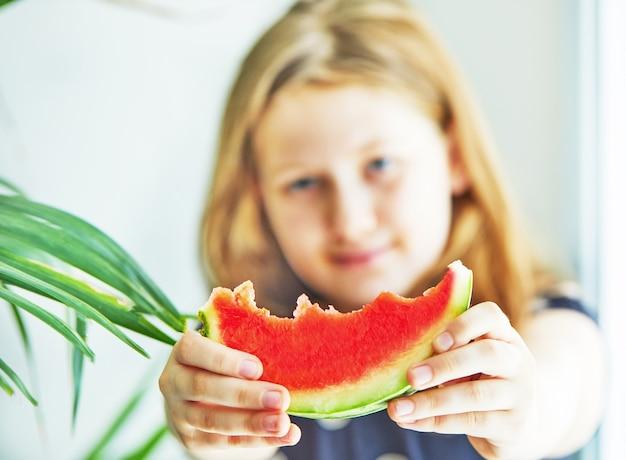 Een tienermeisje in een blauwe jurk met polka dots met een plakje watermeloen in haar uitgestrekte armen selectieve aandacht