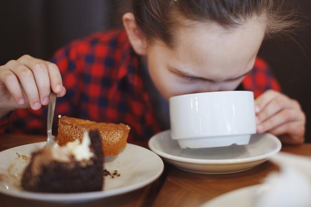 Een tienermeisje in een geruit overhemd in een café drinkt thee en eet een cake.