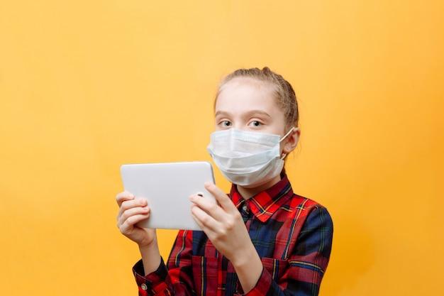 Een tienermeisje in een medisch masker op een gele muur houdt een tablet-pc