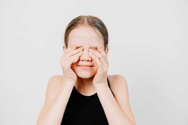 Een tienermeisje in een zwart t-shirt sluit haar ogen met haar handen tegen de witte muur. wachten op een verrassing of een onwil om te zien. kijkverbod voor kinderen.