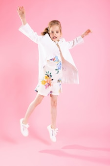 Een tienermeisje in lichte kleren sprong op een roze achtergrond.