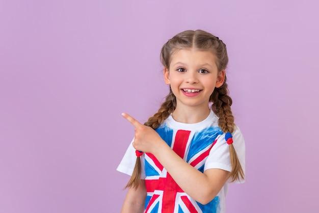 Een tienermeisje met een afbeelding van de vlag van groot-brittannië op haar t-shirt wijst met haar vinger naar de zijkant.