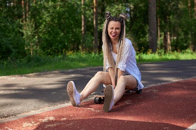 Een tienermeisje met lange blonde staartjes zit op een longboard en toont vrolijk haar tong jeugdp...