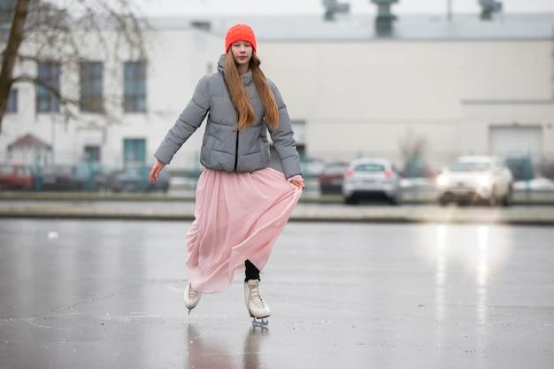 Een tienermeisje schaatst op het ijs in de stad.