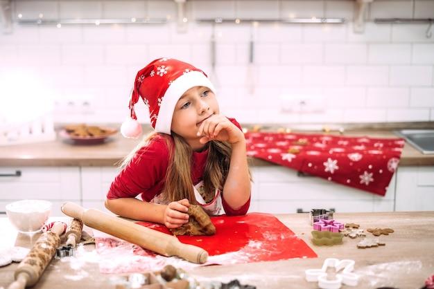 Een tienermeisje staat in de keuken aan de tafel en bereidt deeg voor bakken