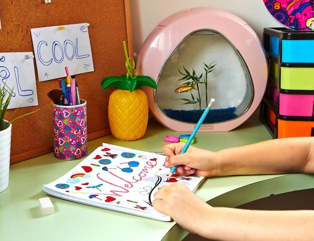 Een tienermeisje tekent in haar kamer