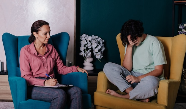 Een tienermeisje zit in een stoel bij een receptie met een vrouwelijke psycholoog