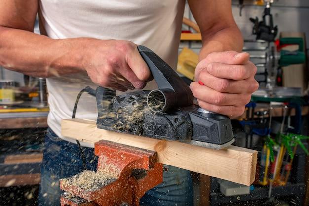 Een timmerman werkt aan de houtbewerking van de werktuigmachine. zaagt meubeldetails met een cirkelzaag