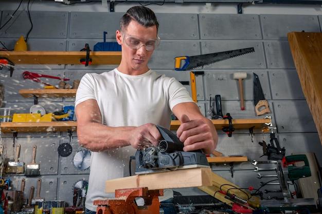 Een timmerman werkt aan houtbewerking van de werktuigmachine. zaagt meubeldetails met een cirkelzaag. proces om delen in delen te zagen.