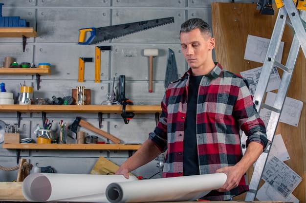 Een timmerman werkt. timmerman die tekenproject bestudeert. tegen de achtergrond van de workshop.