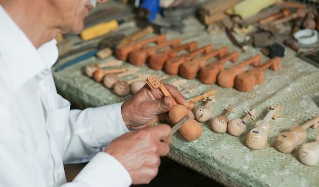 Een timmermansmeester die hout snijdt en figuren van teerinstrumenten maakt