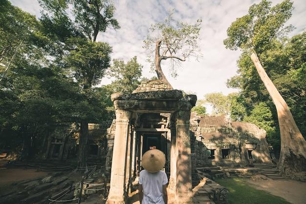 Een toerist bezoekt angkor ruïnes te midden van jungle