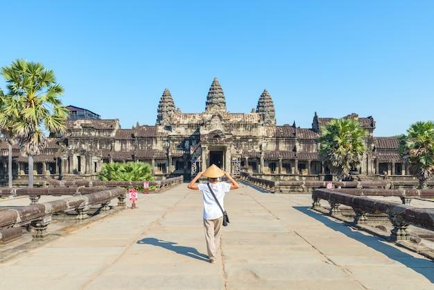 Een toerist die de ruïnes van angkor wat bezoekt bij zonsopgang