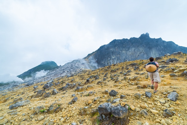 Één toerist die sibayak-vulkaan, actieve caldera die, sumatra indonesië stomen beklimt