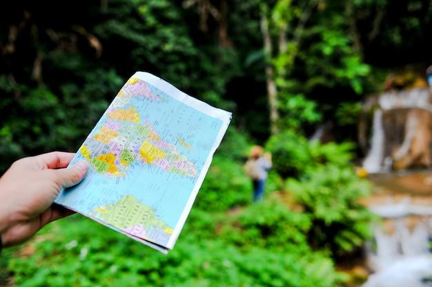 Een toerist en zijn kaart op een reis naar het bos in thailand.
