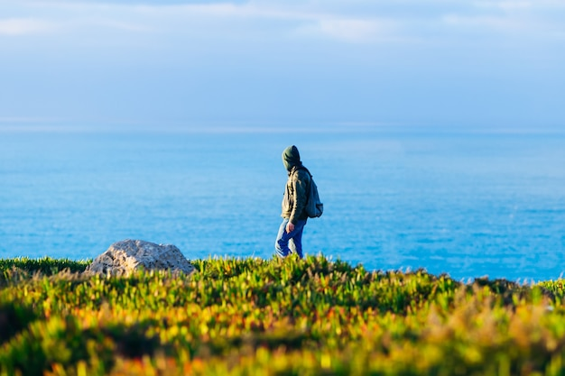 Een toerist in een groene trui met capuchon die op de schilderachtige oever van de oceaan loopt