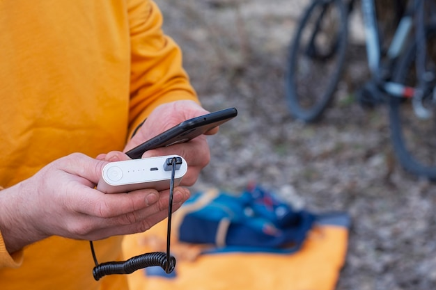 Een toerist laadt een smartphone op met een powerbank op de achtergrond van een rugzak en een fiets in de natuur.