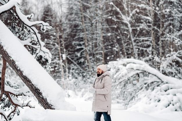 Een toerist loopt in een met sneeuw bedekt bos. winterbos in estland. reis door het winterbos.