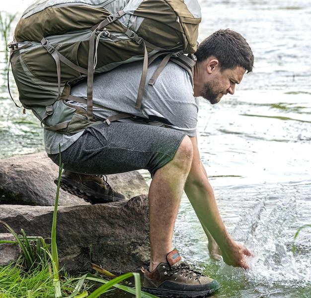 Een toerist met een grote wandelrugzak in de buurt van een bergrivier in de zomerhitte.