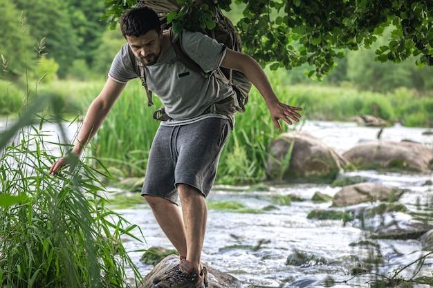 Een toerist met een grote wandelrugzak koelt af in de buurt van een bergrivier in de zomerhitte.