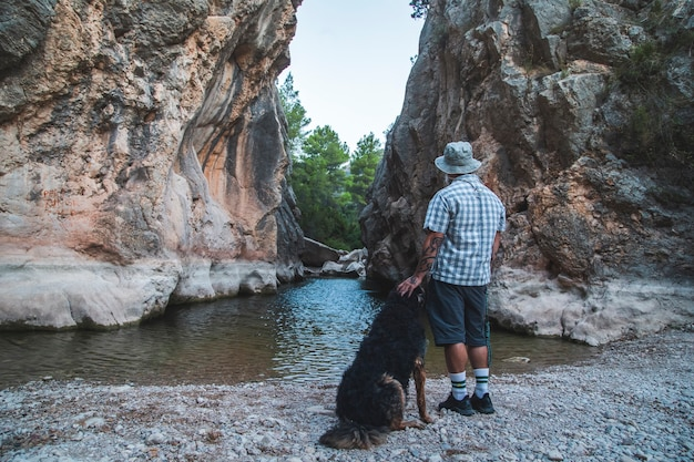 Een toerist met een huisdier met zijn rug naar de camera op de rivieroever