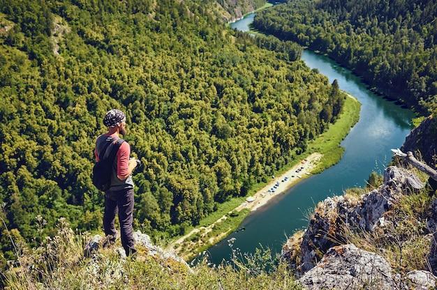 Een toerist met een rugzak op een rots genieten van een uitzicht op de vallei van de rivier