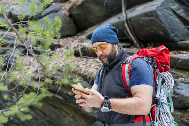 Een toerist met een rugzak staat bij een steile rots en myotrieten in het scherm van een mobiele telefoon. zoekt een weg met behulp van gps-navigator. het concept van reizen, overwinnen en een actieve levensstijl