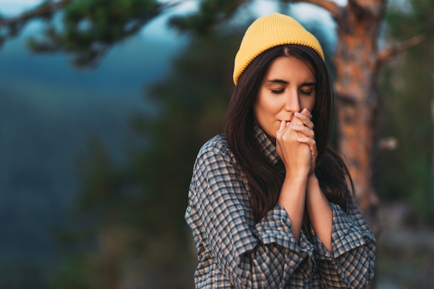 Een toerist verwarmt haar handen. de handen van een vrouwelijke reiziger bevroor in de bergen. portret van een reizigersmeisje in een gele pet. portret van een vrouwelijke toerist. het meisje is een toerist. ruimte kopiëren