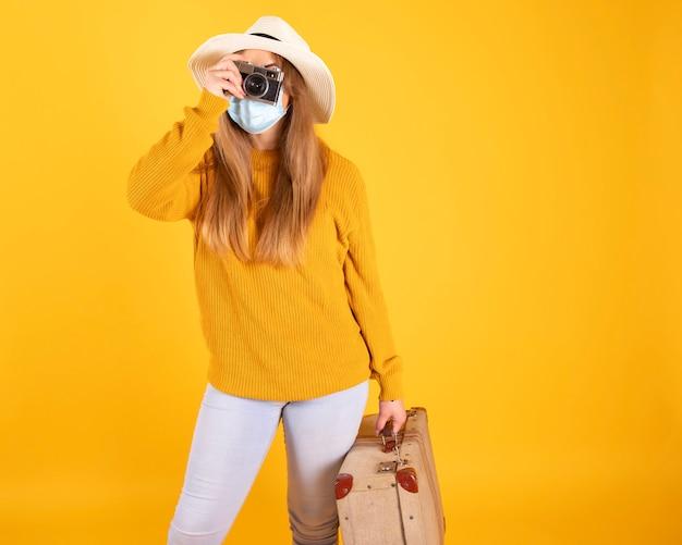 Een toeristenmeisje met een medisch masker, koffer en camerahoed kan niet reizen met covid-19