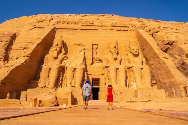 Een toeristenpaar dat de tempel van abu simbel in zuidelijk egypte in nubië bezoekt naast het nassermeer. tempel van farao ramses ii, reislevensstijl