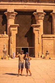 Een toeristenpaar verlaat de edfu-tempel bij de rivier de nijl in aswan. egypte