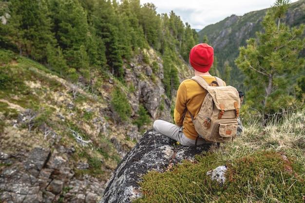 Een toeristenreiziger met rugzak en rode hoed zit op de rand van een klif en kijkt op bergen