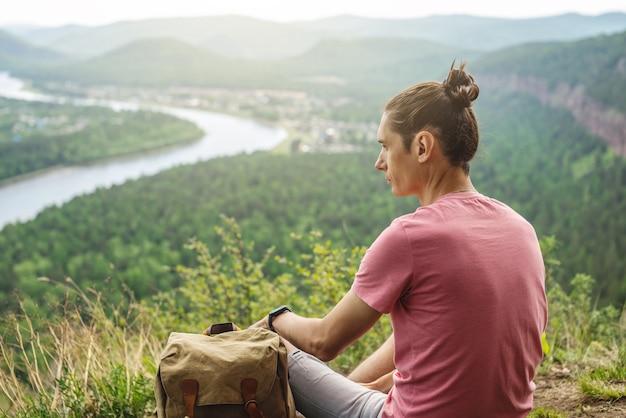 Een toeristenreiziger met rugzak zit op de rand van een klif en kijkt uit over een groene bosvallei met de rivier