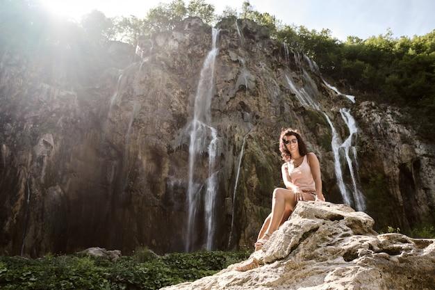 Een toeristenvrouw bij de grote waterval in het nationale park van plitvice, kroatië