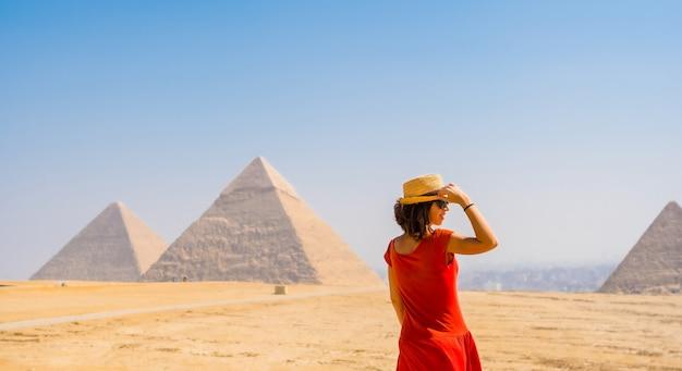 Een toeristisch meisje in een rode jurk kijkt naar de piramides van gizeh, het oudste grafmonument ter wereld. in de stad caïro, egypte