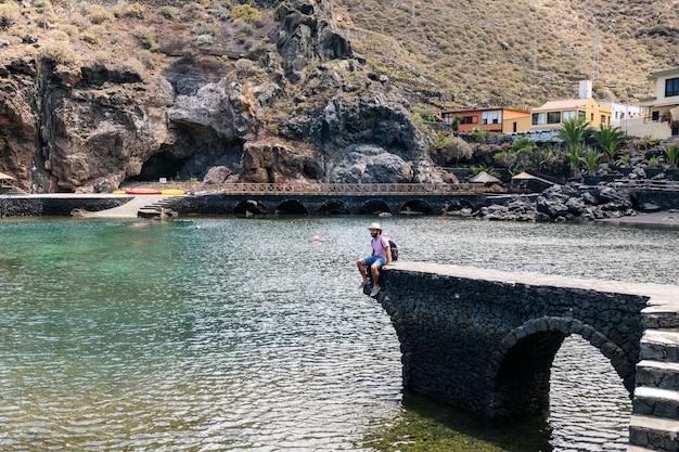 Een toeristische man met hoed en rugzak door een dorp aan de kust van el hierro, canarische eilanden