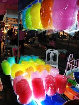 Een toonbank die gekleurde suikerspin verkoopt op een nachtelijke straatvoedselmarkt in azië.