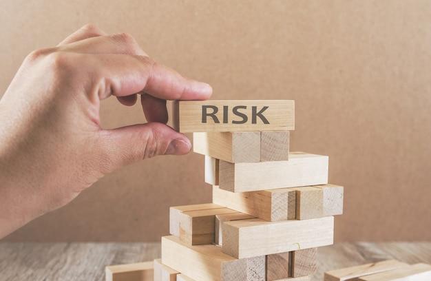 Een toren van houten blokken en de handen van een man kiezen een blok waarop het woord risico staat geschreven