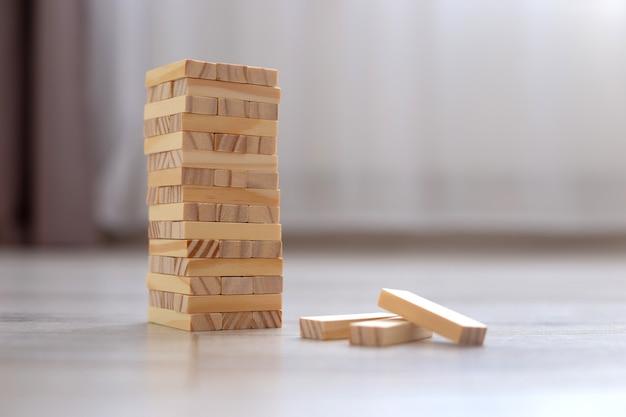 Een toren van houten blokken op de vloer in de kamer. gezinsbordspellen