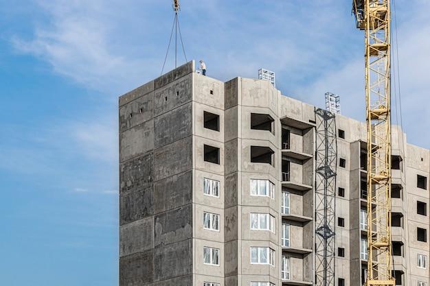 Een torenkraan monteert gootpanelen tijdens de bouw van een paneelhuis. moderne woningbouw. industriële techniek. bouwen van hypotheken.