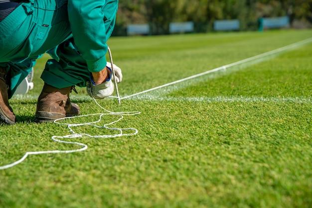 Een touw uitrekken om een voetbalveld te bekleden met witte verf op het gras