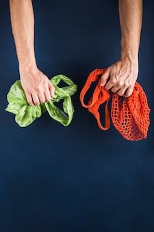 Een touwtas in de hand van de ene man, in de andere een plastic zak