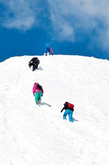 Een touwteam van bergbeklimmers klimt naar de top