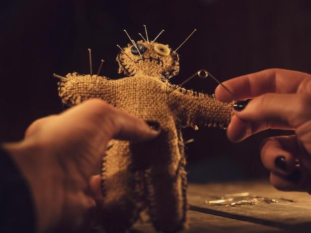 Een tovenares doorboort een voodoo-pop met een speld en veroorzaakt letsel of schade aan een persoon, close-up.