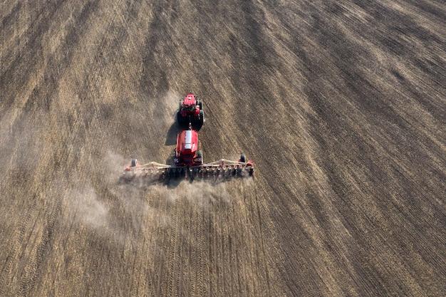 Een tractor bereidt land voor met een zaaiende cultivator op landbouwgrond.